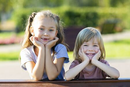 Portrait of a sister and brother of preschool age. A girl and a boy of Caucasian nationality posing in the summer in park, close-up.
