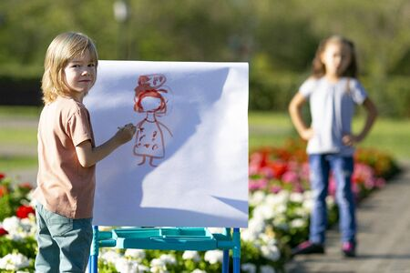 Children paint portraits of each other on the street. Brother and sister paint funny portraits of people with paints on paper
