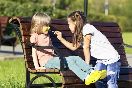 Sister paints on brothers face. A little girl is applying aqua makeup the face of 5 year old boy who is sitting on a bench in a park. Zdjęcie Seryjne