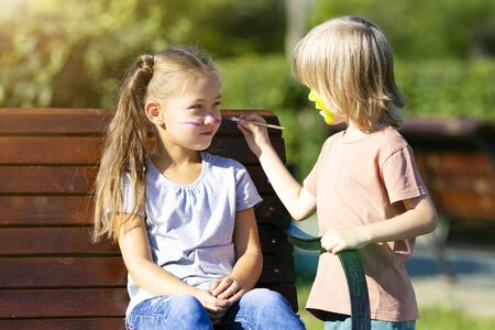 A little boy puts aqua makeup on the face of a 6 year old girl who sits on a bench in the park. Brother paints on sisters face