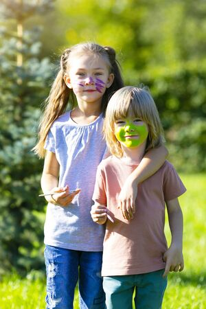 Portrait of a sister with a brother with aqua makeup on their face. Boy and girl with painted faces.