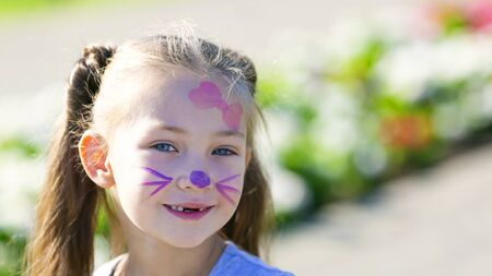 Cute girl with a pattern on her face. A preschool girl with paints on her face is smiling on street Zdjęcie Seryjne