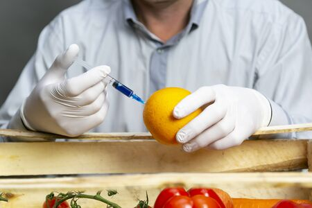 A man injects chemicals into an orange, pesticides and fertilizers and chemicals with a syringe to increase the shelf life of the fruit.