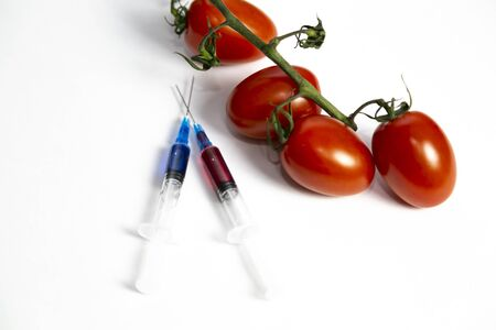 Two syringes with chemicals near a branch of tomatoes. Syringes with chemicals for fertilizing tomatoes on a white background.