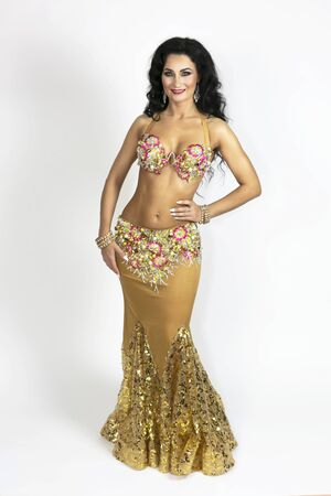 Oriental dancer in clothes gold color with black hair and bronze skin gracefully posing on a white background.