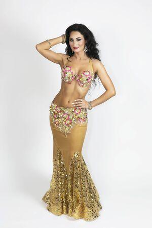 Ropa de bailarina oriental de color dorado con cabello negro y piel bronceada elegantemente posando sobre fondo blanco.