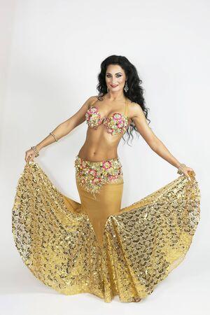 Bailarina oriental en ropa de color dorado con cabello negro y piel bronceada elegantemente posando sobre un fondo blanco. Una mujer morena con un traje de baile sobre un fondo blanco.