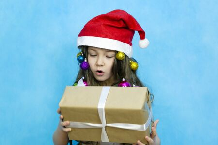 A child in a red hat with a New Years gift in his hands. Girl in a Christmas hat with toys in her hair holds a gift in paper packaging on a blue background.