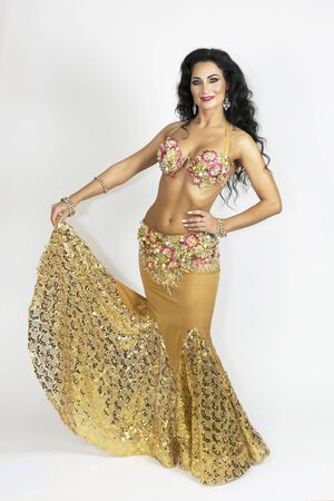 A brunette woman in a dance suit on a white background. Oriental dancer in clothes of gold color with black hair bronze skin gracefully posing on a white background.