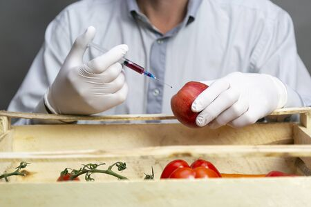 A man injects chemicals into an orange, pesticides and fertilizers and chemicals with a syringe to increase the shelf life of the fruit Chemical processing of fruits, fertilizers and pesticides