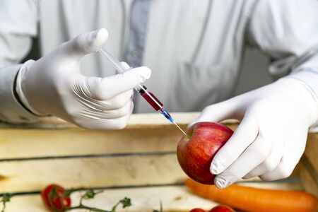 Chemical processing of fruits, fertilizers and pesticides A man injects chemicals into an orange, pesticides and fertilizers and chemicals with a syringe to increase the shelf life of fruit