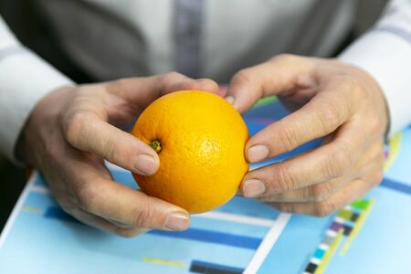 Hands with orange over sales growth graph. Farmer businessman considers the profits and expenses of the harvest of oranges.