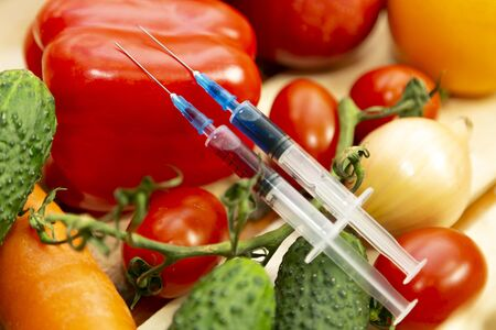 Syringes with chemicals on vegetables Two syringes with nitrates and pesticides lie on a box vegetables and fruits