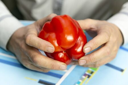 Hands with pepper over sales growth chart. Farmer businessman considers the profit and costs of the harvest of bell pepper.