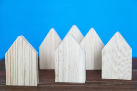 Model of a small village of several houses. Six symbolic houses made of light wood on a blue background. Zdjęcie Seryjne