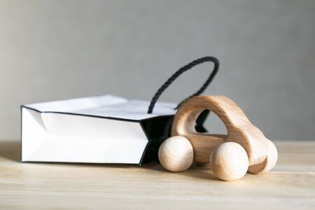 Car is the best gift concept. A wooden car model leaves a gift box on a table.
