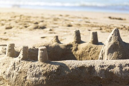 The sand palace was built by children on the sea coast. Sand castle on the beach.