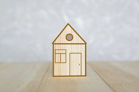House made of light wood on a blue background. A small toy house stands on a wooden surface. Zdjęcie Seryjne