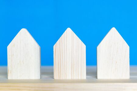 Three wooden houses on a blue background. Models of residential buildings stand on a wooden surface.