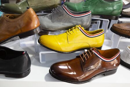 Leather shoes in different colors. Leather mens shoes in leather of different colors on the counter of the store.