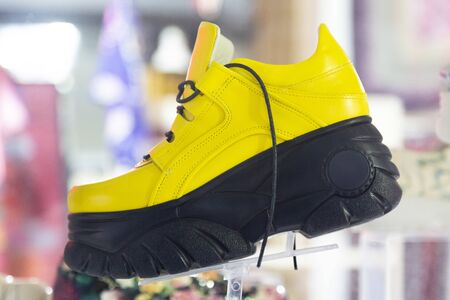 Yellow high-soled shoes in a store. Very high big sole on yellow womens shoes.