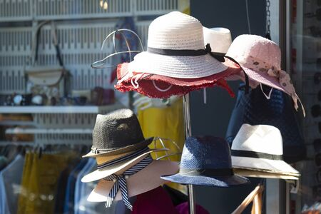 Womens hats are sold outside. Street sales of womens hats., A hanger with a large assortment