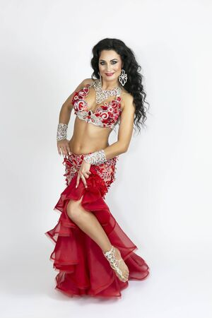 Brunette in beautiful long red dress to perform belly dance on a white background.