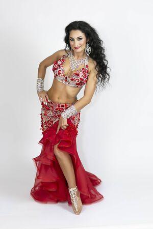 Morena con un hermoso vestido largo rojo realiza danza del vientre sobre un fondo blanco. Chica con un vestido rojo para bailes orientales.