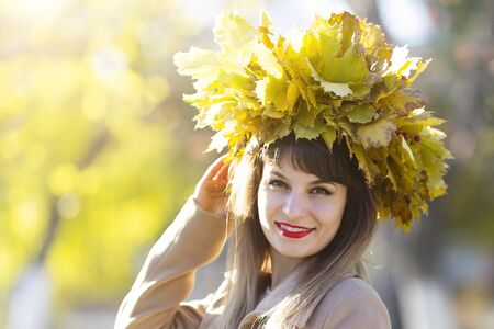 Girl with a wreath of leaves on her head The woman made hat from autumn fallen leaves for the head