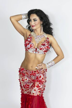 Brunette in a beautiful long red dress perform belly dance on a white background