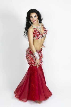 Brunette in a beautiful long dress to perform belly dance on a white background Girl in a red dress for oriental dancing.
