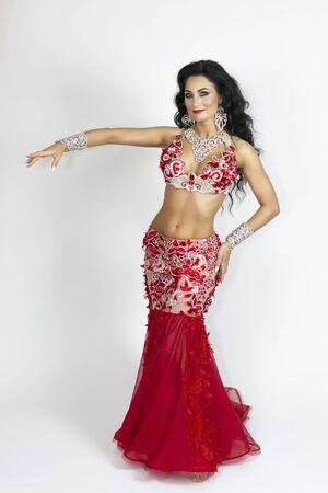 Chica con un vestido rojo para bailes orientales. Morena hermoso vestido largo rojo para realizar danza del vientre sobre un fondo blanco.