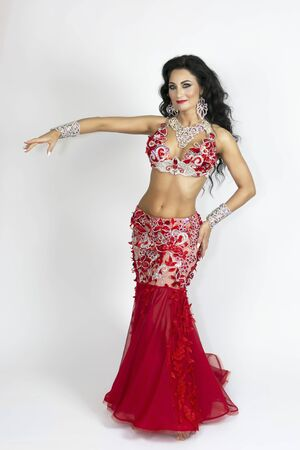 Girl in a red dress for oriental dancing. Brunette beautiful long red dress to perform belly dance on a white background