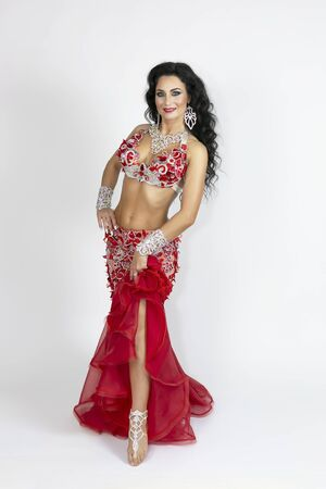 Brunette a beautiful long red dress to perform belly dance on a white background Reklamní fotografie