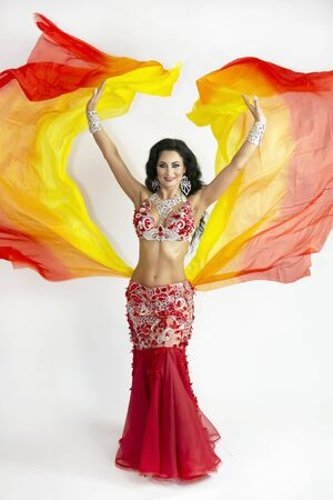 A brunette woman performs a belly dance waving in the air with colored shawls on white background