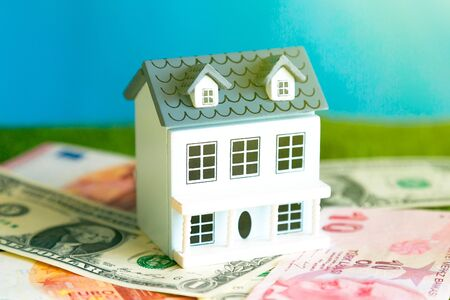 The model of the house is on the spread of money. Residential building stands on banknotes, the concept of the cost of construction and maintenance of real estate.