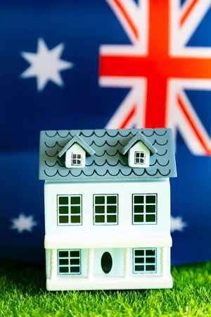 Real estate in the Australia, concept. Model of a residential building, cottage on the background of the flag of England. Reklamní fotografie