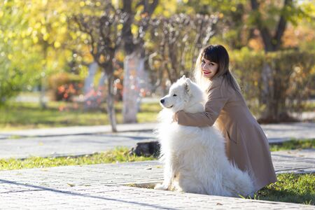The mistress with her dog is dreamily looking into the distance, Young girl hugging her white dog looking at the rising sun