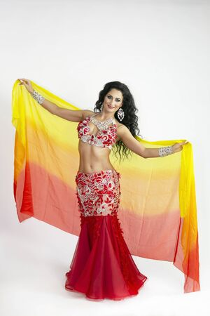 A brunette woman performs a belly dance waving in the air with colored shawls a white background. The dancer of east dances with bright scarfs fabrics.