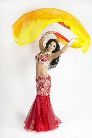 The dancer of east dances with bright scarfs fabrics. A brunette woman performs a belly dance waving in air with colored shawls on a white background.