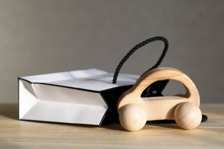 A small car model made of wood next to a gift box, a concept car as a gift. A car as a gift for a loved one.