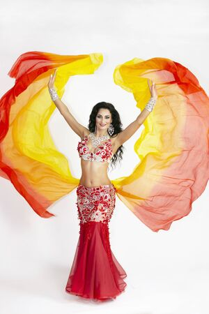 A brunette woman performs a belly dance waving in the air with colored shawls on a white background The dancer of east dances with bright scarfs fabrics. Reklamní fotografie