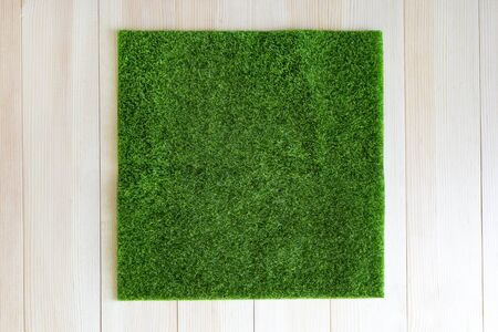 Grass square on wooden background. A piece of green grass in the shape of a square is laid out on a light wooden background.