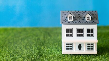 Small cottage on a green lawn. Residential building model stands on green grass, place for an inscription, concept.
