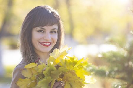 Pretty woman 25-30 years old with black hair a luxurious smile with yellow autumn leaves in her hands