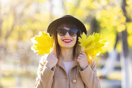Pretty woman 25-30 years old with black hair and luxurious smile with yellow autumn leaves in her hands A brunette woman with an armful of leaves in her hands.
