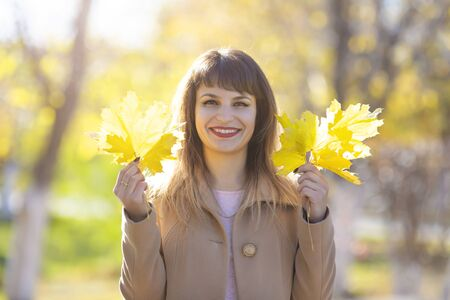 A brunette woman with an armful of leaves in her hands. Pretty woman 25-30 years old with black hair and a luxurious smile with yellow autumn leaves in her hands. Reklamní fotografie