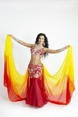 The dancer of east dances with bright scarfs fabrics. A brunette woman performs a belly dance waving in the air with colored shawls on a white background.