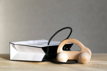 A small car model made of wood next to a gift box, a concept car as a gift.