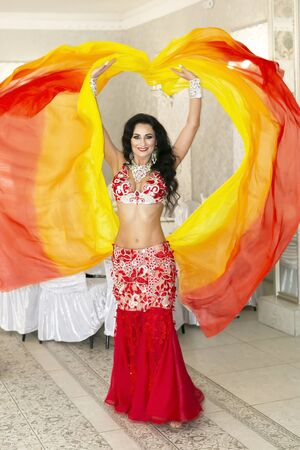 Oriental dancer in a red-yellow dress. Belly dancer throws the ends of her beautiful orange skirt into the air.